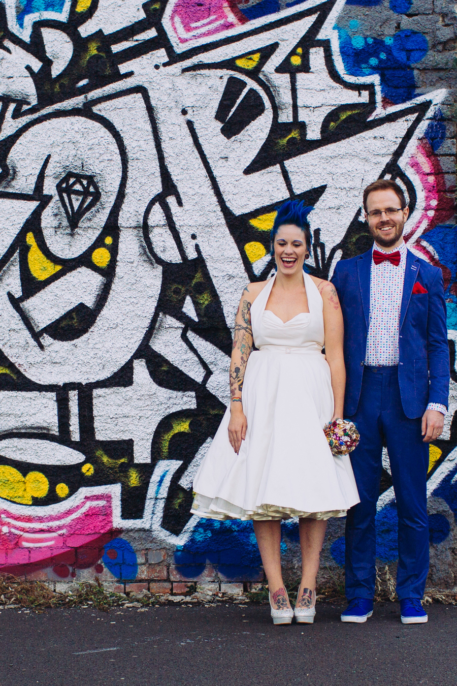 Alternative Wedding Photographer Northern Ireland, rockstar bride and groom laughing beside pink and blue graffiti, Belfast