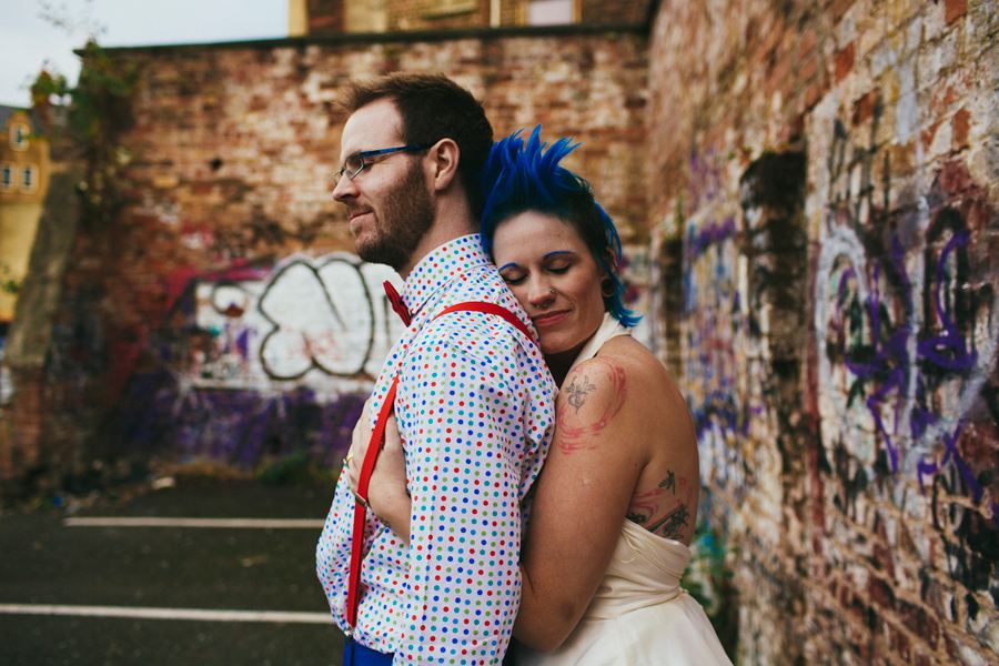Alternative Wedding Photographer Northern Ireland, bride hugging groom with polka dot shirt, red braces and red bow tie, beside brick wall with graffiti, Belfast