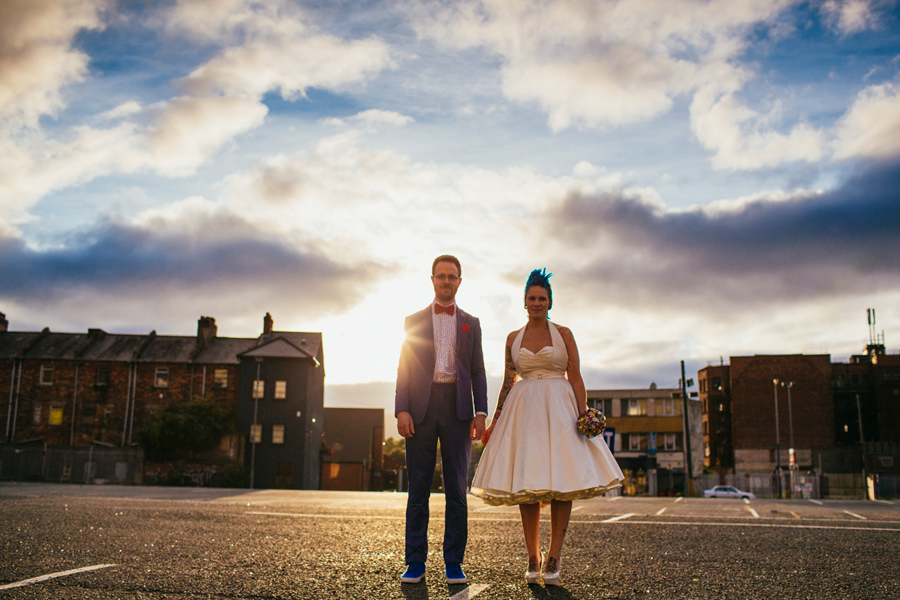 Alternative Wedding Photographer Northern Ireland, geek groom and suicide girl bride holding hands in the sunset, sun flare blue sky and white fluffy clouds, Smithfield and Union Quarter, Belfast
