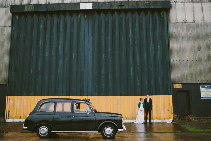 Alternative Wedding PhotographeyNorthern Ireland, bride and groom with black taxi, Titanic Quarter, Belfast, Ireland.