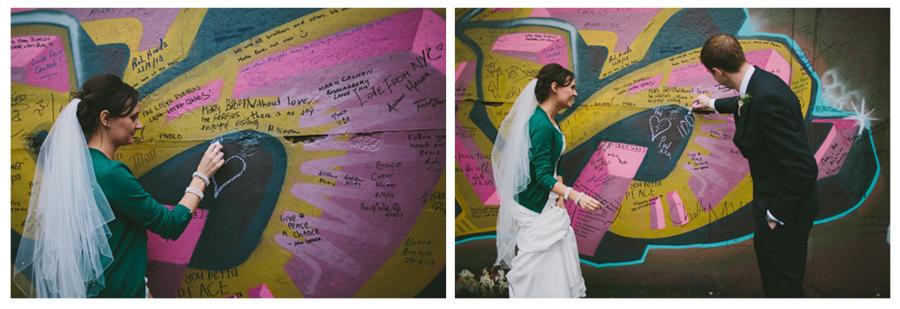 Alternative Wedding Photographer Northern Ireland, bride and groom write on Peacewall, Belfast