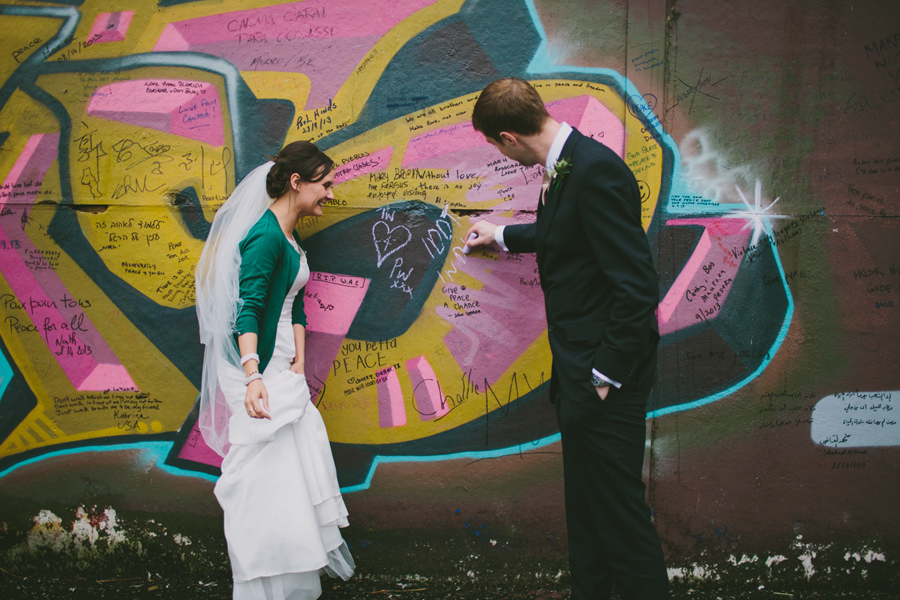 Alternative Wedding Photography Northern Ireland, bride and groom writing on Peacewall, Belfast