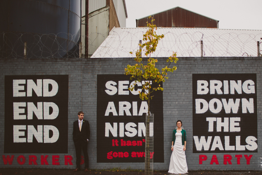 "Wedding Photography Northern Ireland, bride and groom stand at political mural, Belfast, "" End Sectarianism"", Northern Ireland."