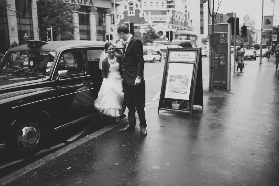 Alternative Wedding Photographer Northern Ireland, bride and groom getting out of Black Taxi, Great Victoria Street, Belfast