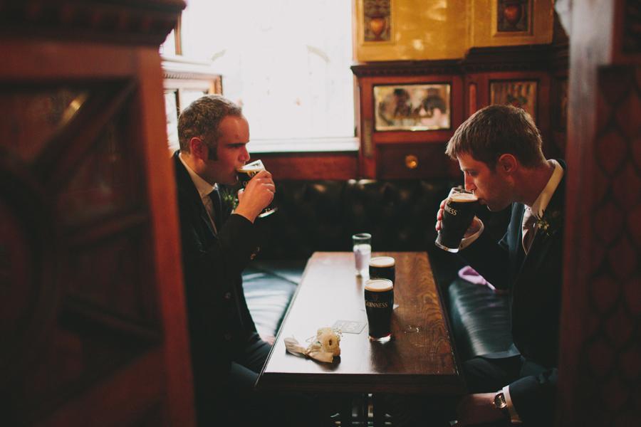 Irish Wedding Photographer, groom and best man drink a pint of Guinness, Crown Bar, Belfast , Northern Ireland.
