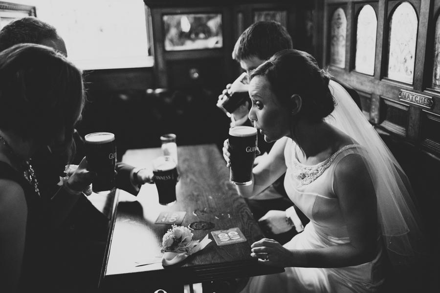 Wedding Photography Northern Ireland, irish bride drinks Guinness, Crown Bar, Belfast, Ireland.