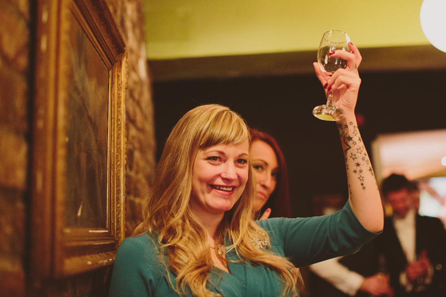 Alternative Wedding Photographer Northern Ireland, tattoo wedding guest gives toast at wedding reception, Barking Dog, Belfast.