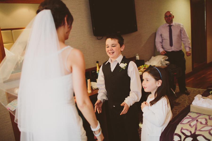 Wedding Photography Northern Ireland, kids hug their aunt in wedding dress, Europa Hotel, Belfast.