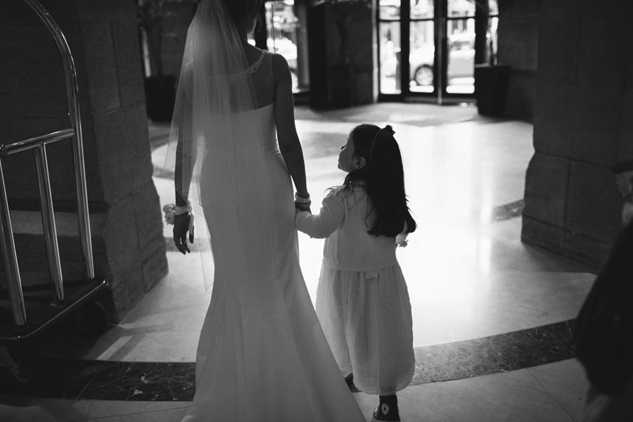 Wedding Photographer Northern Ireland, bride walks with flower girl into lobby of Europa Hotel, Belfast, Northern Ireland.