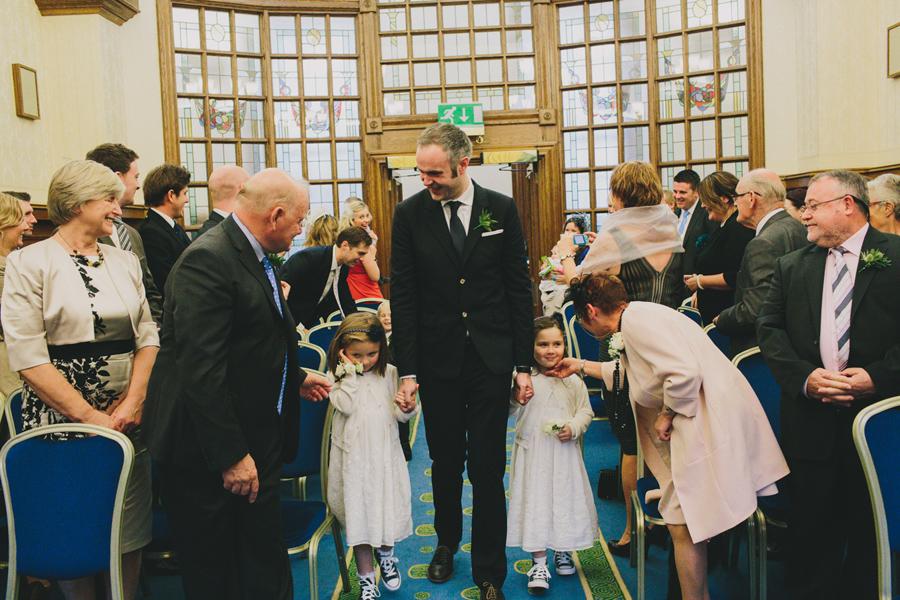 Alternative Wedding Photography Northern Ireland, best mas walks down aisle with flower girls, Belfast City Hall.