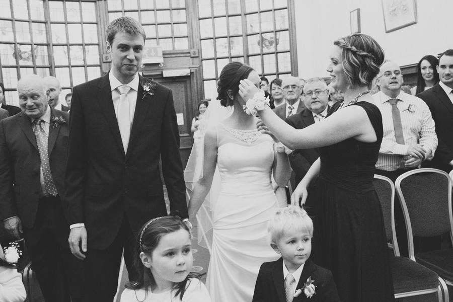 Wedding Photography Northern Ireland, bridesmaid fixes brides hair, Belfast City Hall, Northern Ireland.