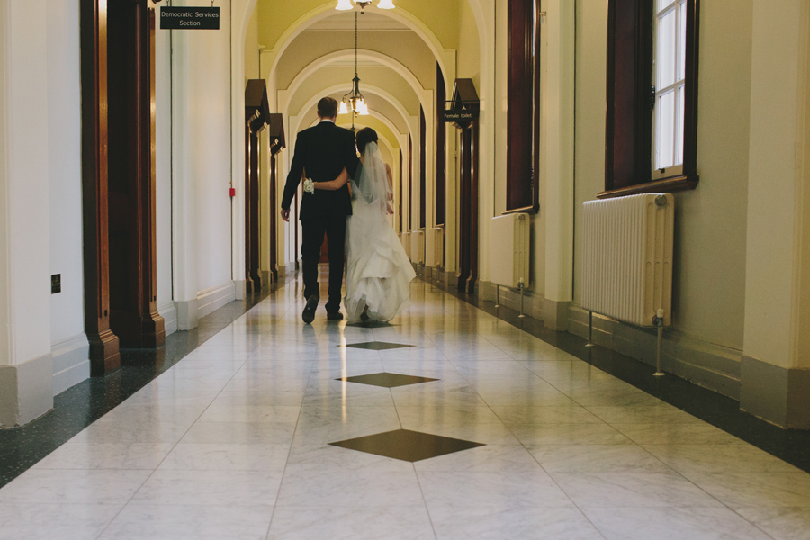 Wedding Photography Northern Ireland, newly wed bride and groom walk though Belfast City Hall.