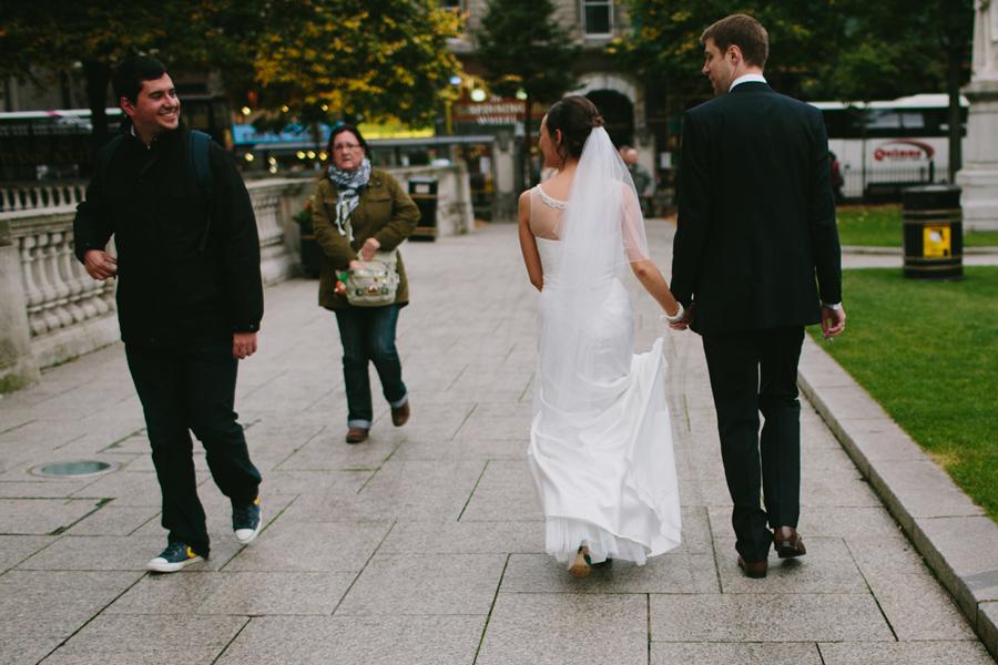 Wedding Photographer Northern Ireland, bride and groom walking through city, Belfast, N. Ireland.