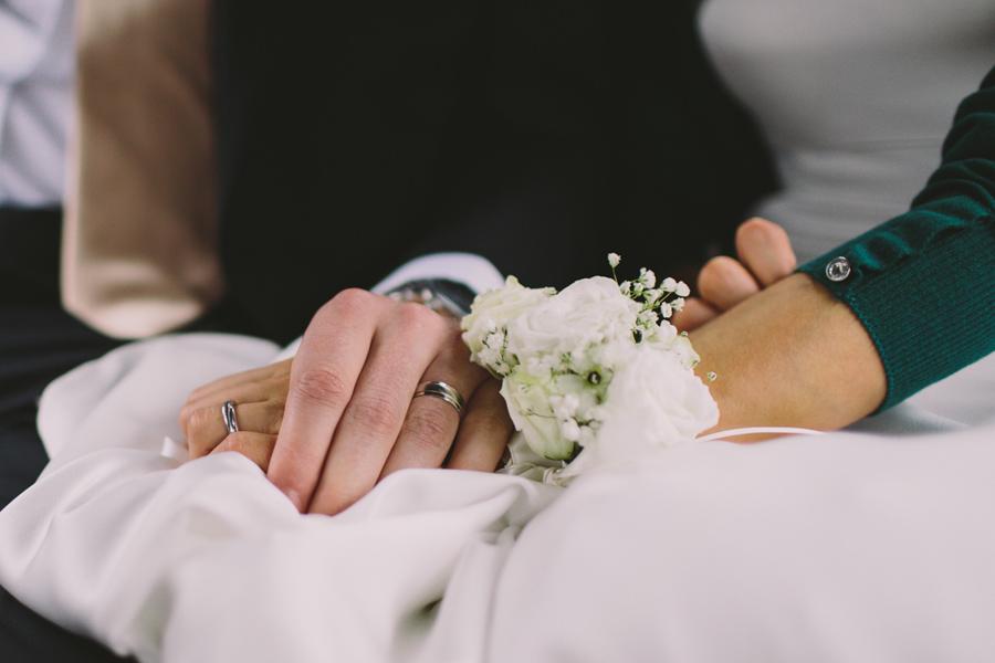 Wedding Photographer Northern Ireland, Groom holds brides hand in Belfast Black Taxi, Northern Ireland.