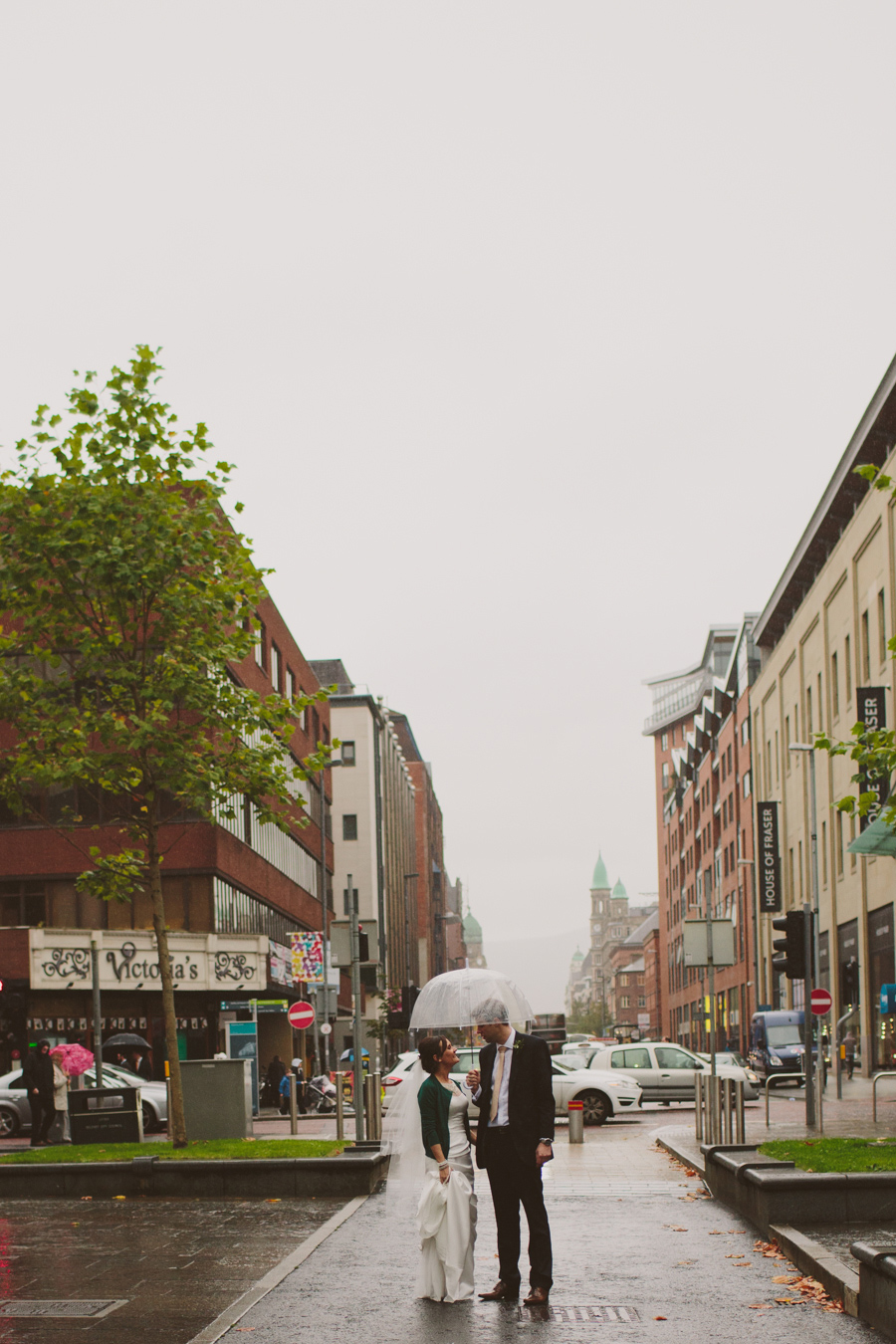 Wedding Photographer Northern Ireland, bride and groom stand in the rain, Belfast, Northern Ireland.