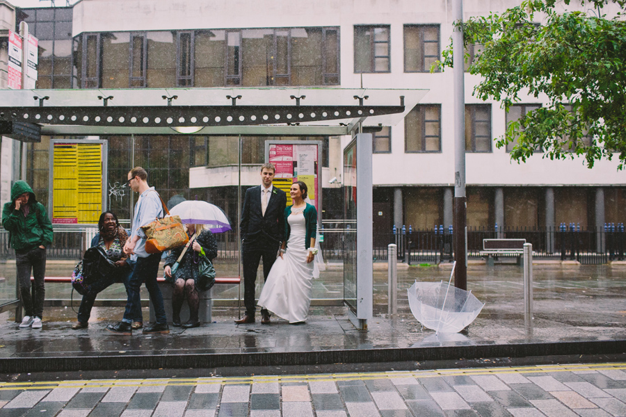 Wedding Photography Northern Ireland, bride and groom wait for a bus in the rain, Belfast .