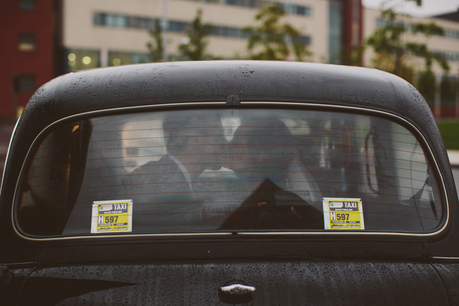 Alternative Wedding Photographer Northern Ireland, bride and groom kiss in the back of a black taxi, Belfast.