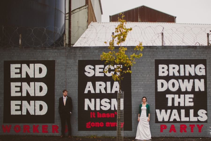 Wedding Photography Northern Ireland, bride and groom with political mural, end sectarianism, Belfast