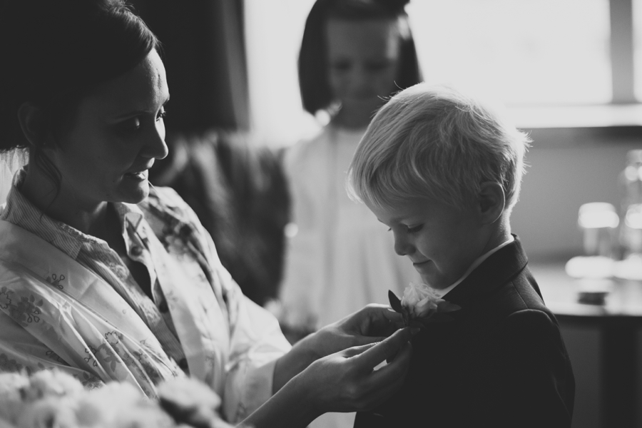 Wedding Photographer Northern Ireland, bride pins buttonhole to page boy, Europe Hotel Belfast.