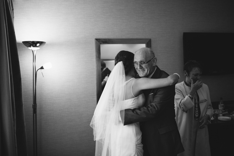 Wedding Photographer Northern Ireland, bride hugs grandfather, Europa Hotel, Belfast.
