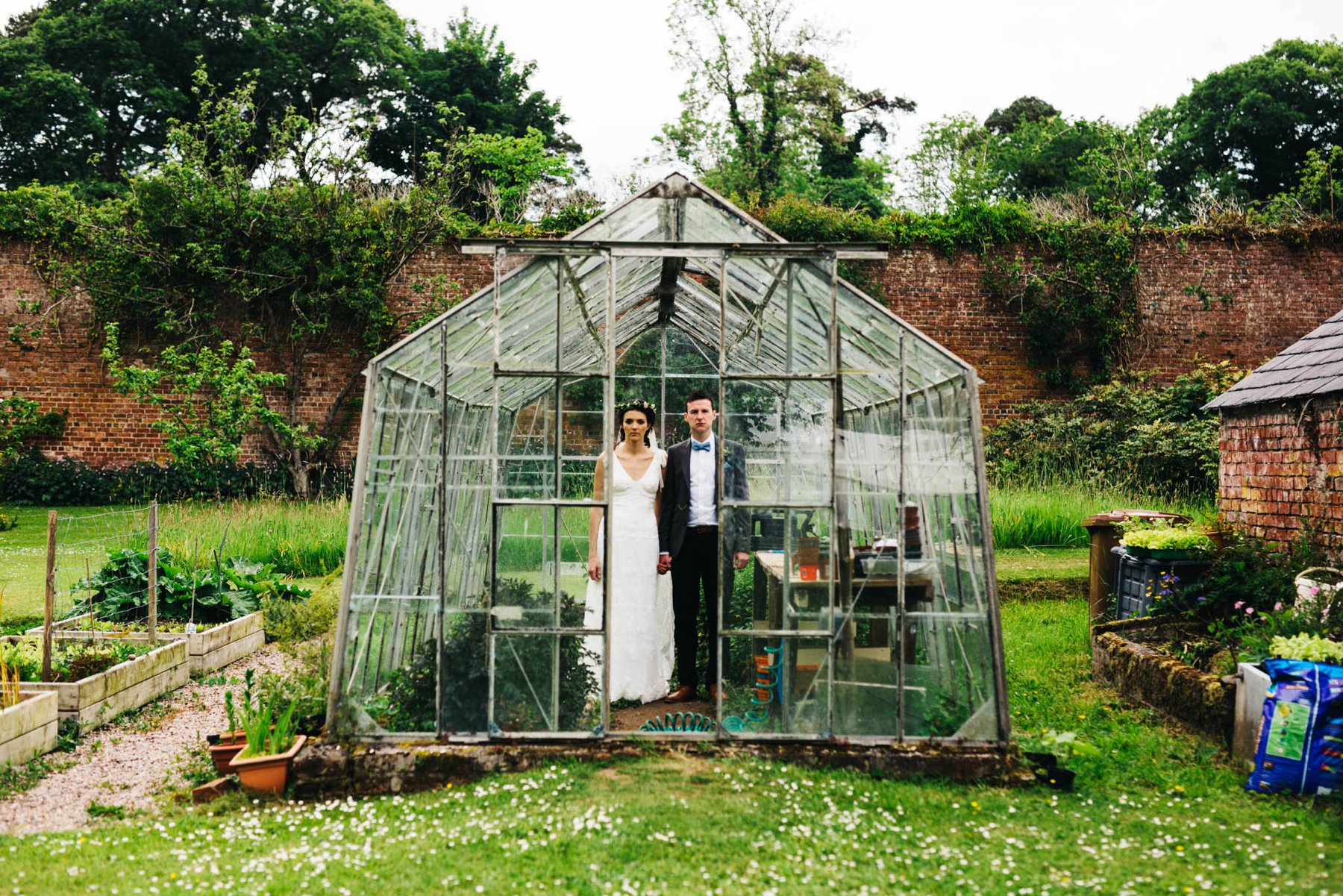 Bride and Groom pose for their wedding portrait in a greenhouse on the grounds of Ballyscullion, Northern Ireland