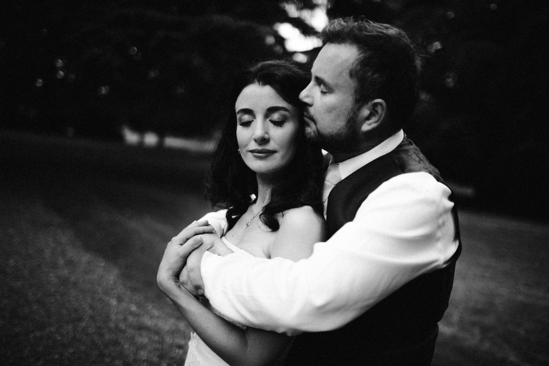 black and white showing bride and groom in embrace for wedding portrait
