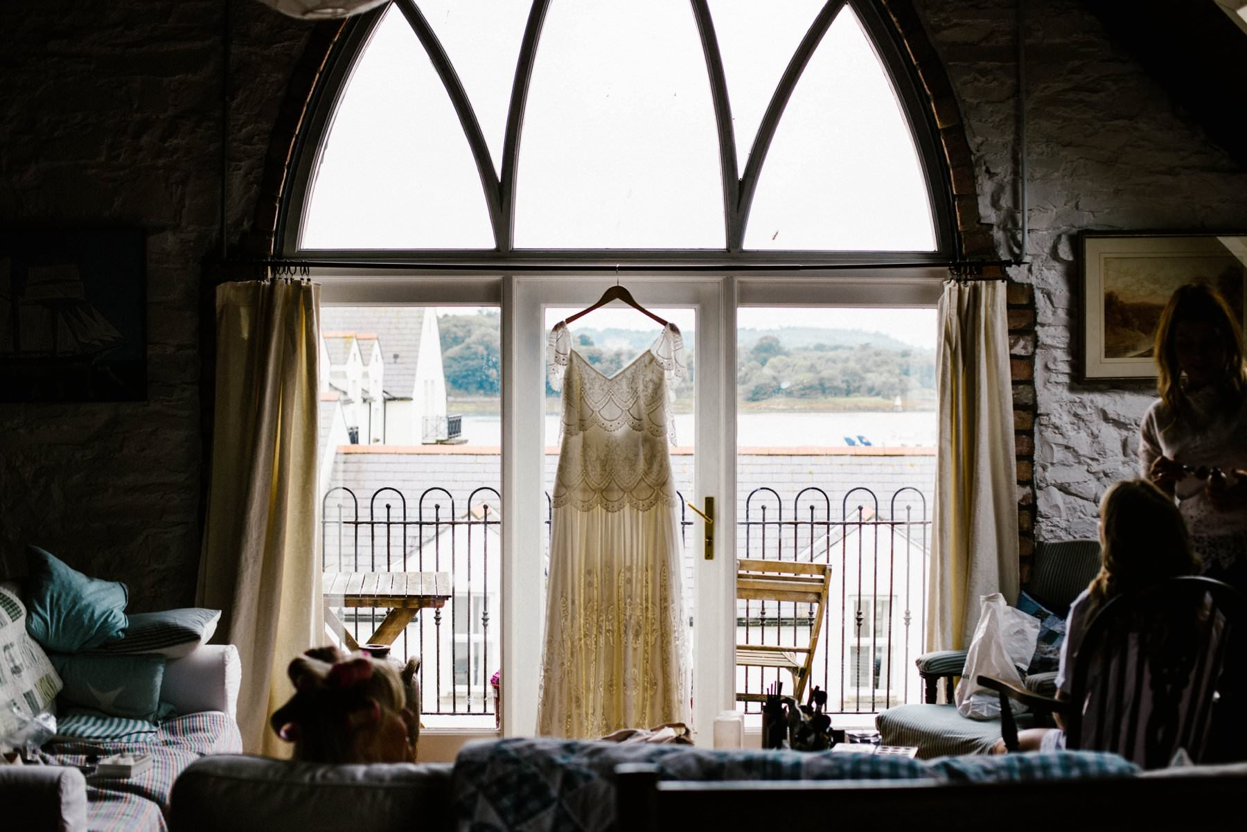 brides dress hanging in window wedding photographer northern ireland