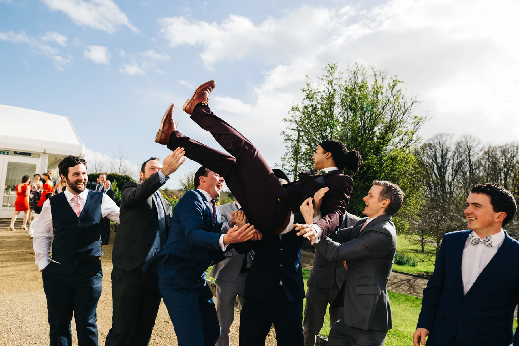 groom thrown up in the air by friends wedding photography ireland