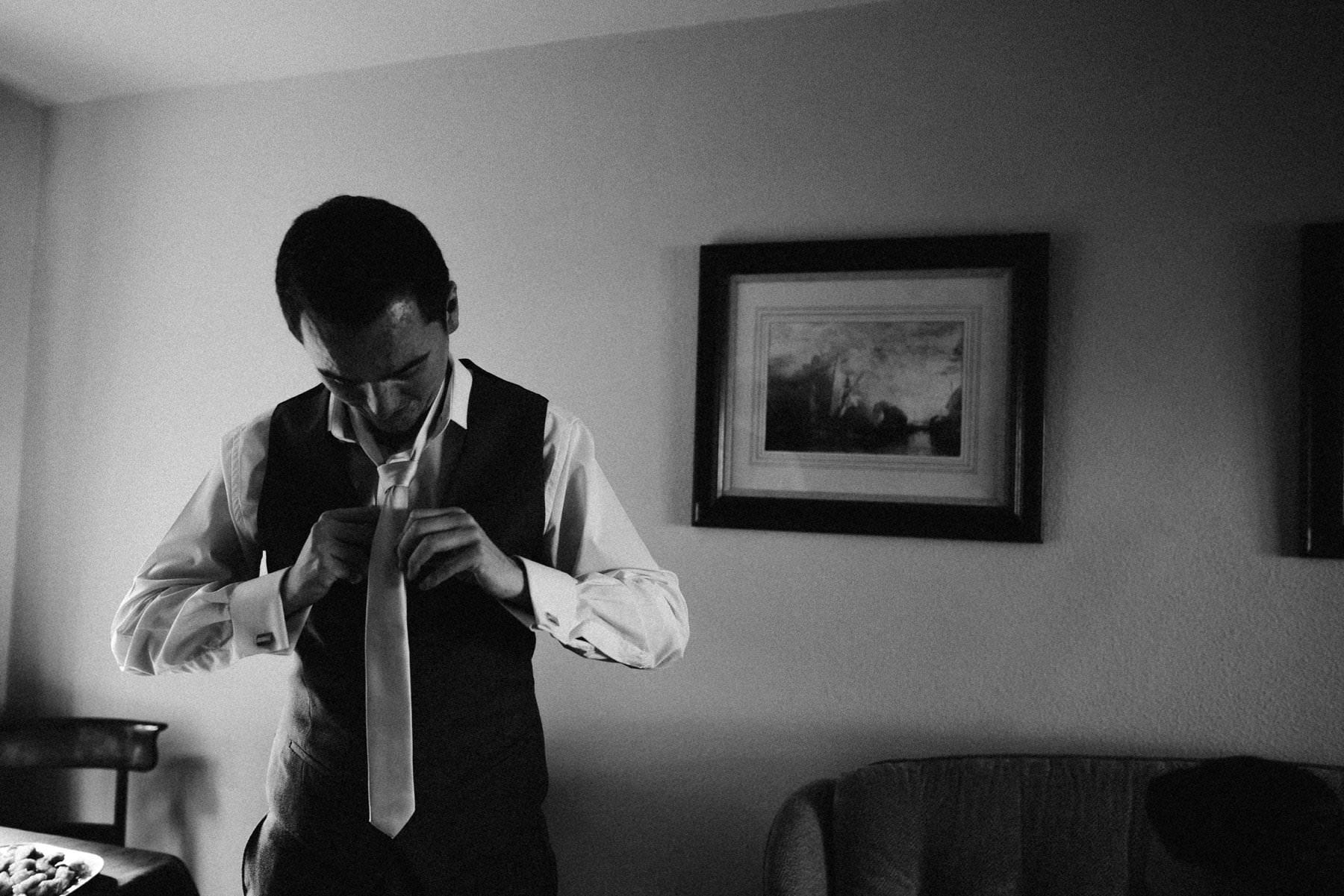 groom ties his tie on wedding morning, wedding photography northern ireland