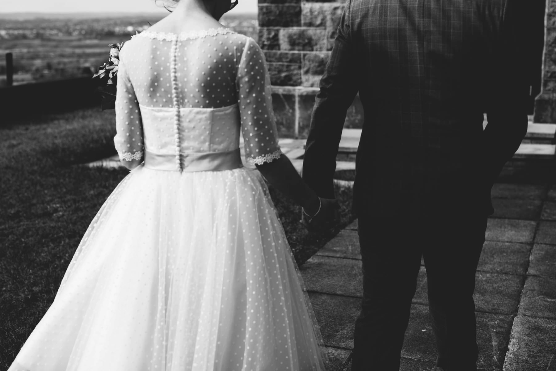 bride and groom hold hands black and white wedding photography northern ireland