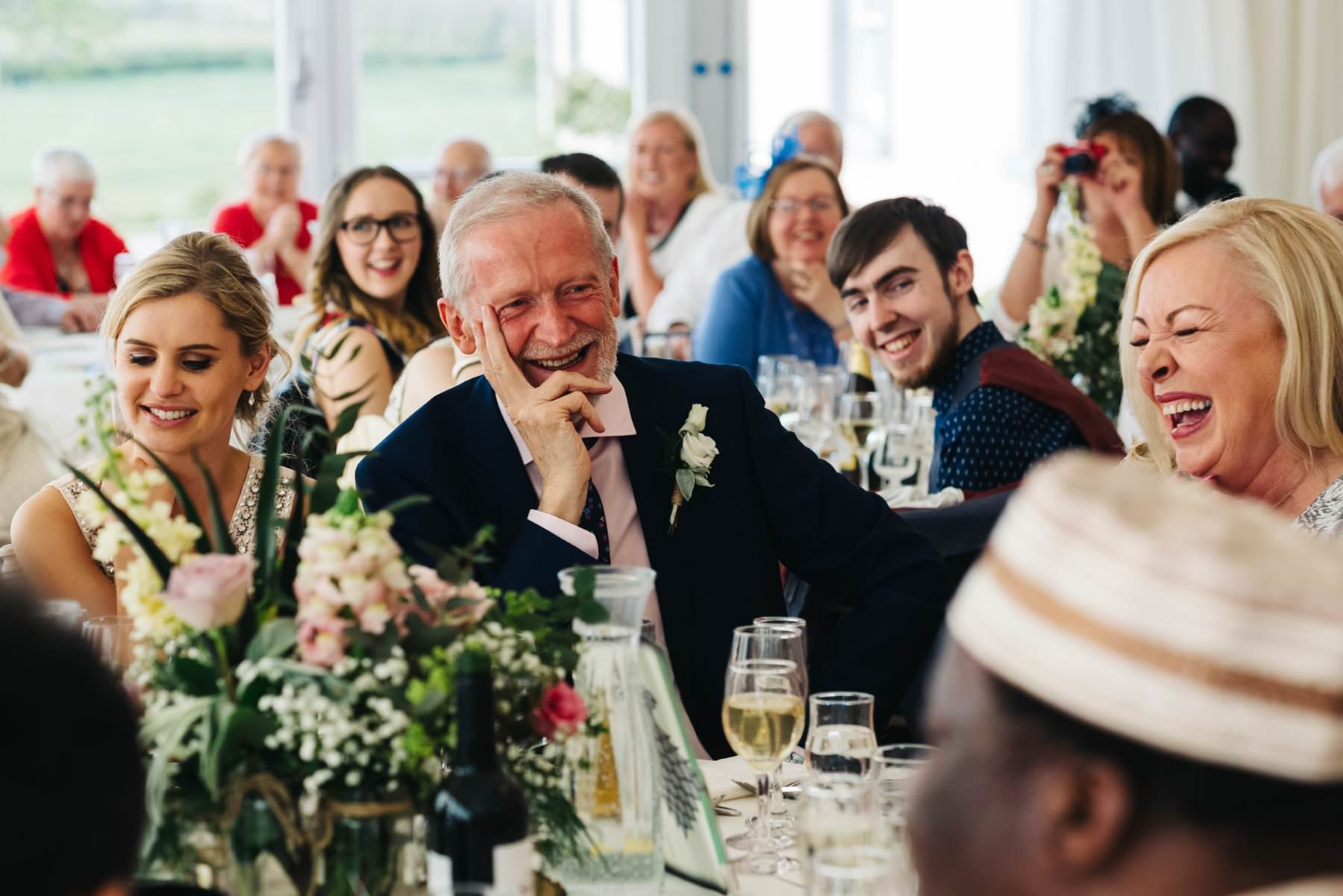 guests laughing at during a speech at clonabreany house wedding photography ireland