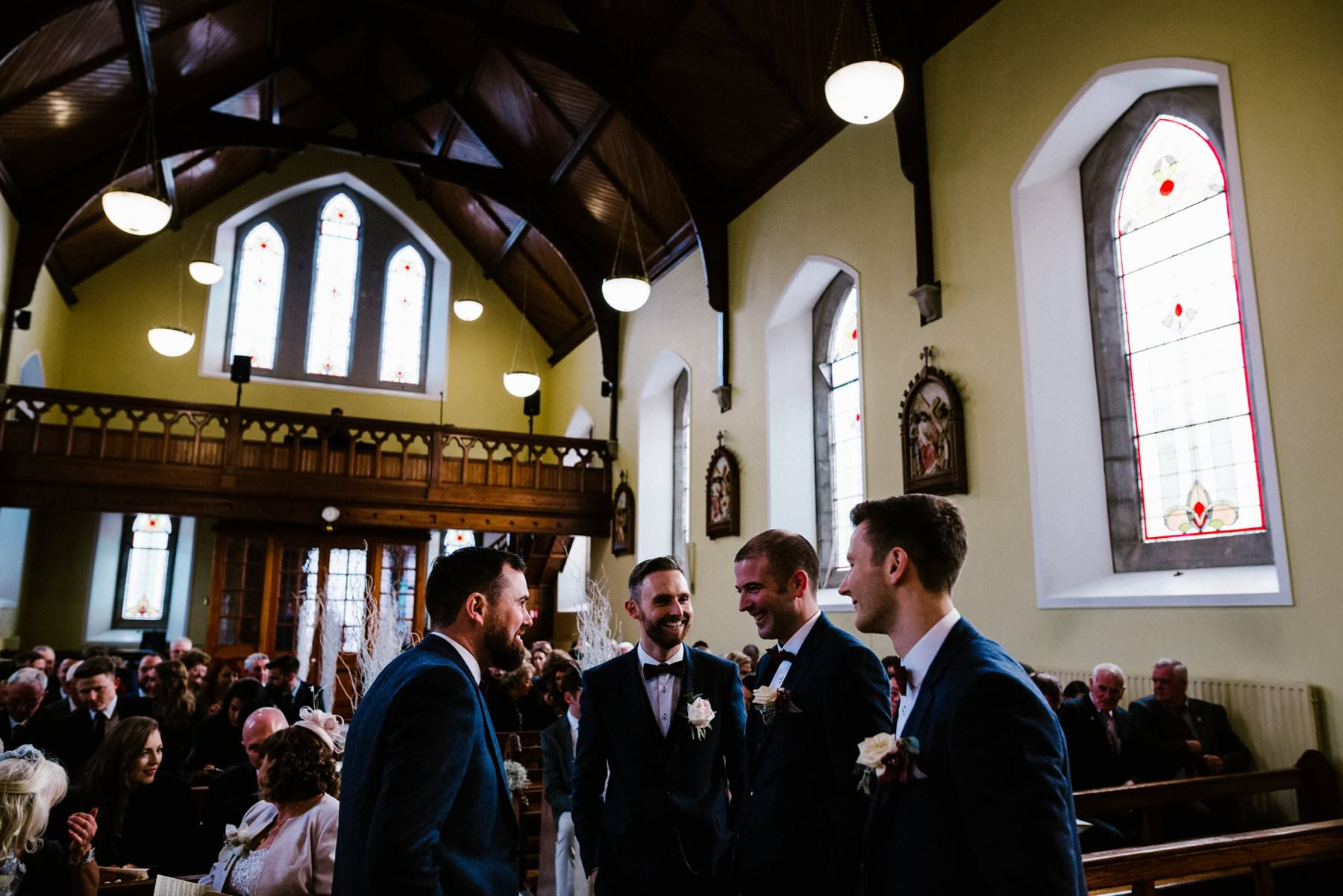 groom waiting with groomsmen at front of church wedding photographer ireland