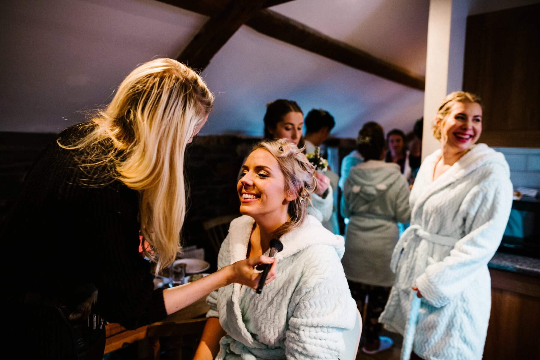 Bride has make up applied in the cottages of Larchfield Estate