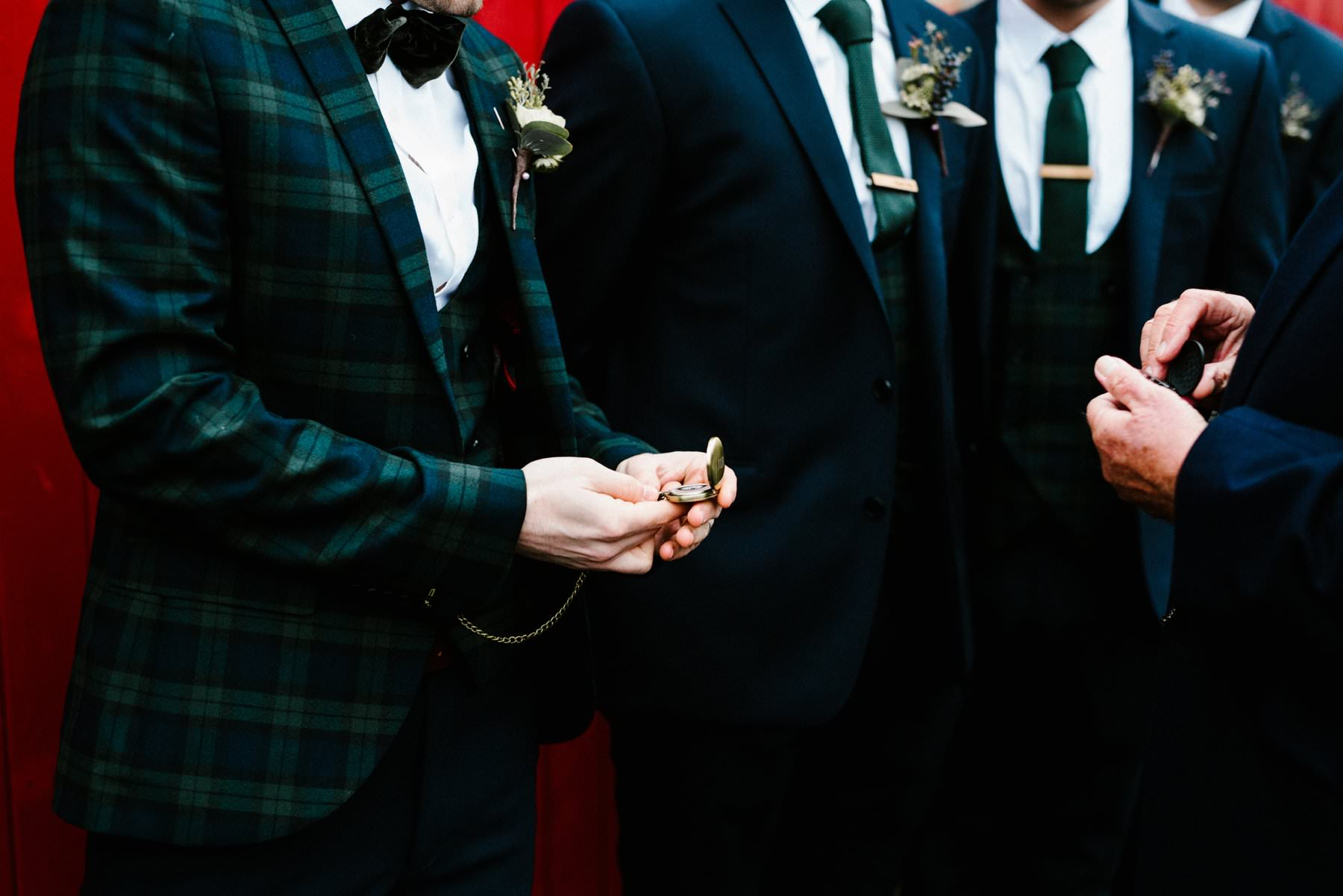 groom shows off his pocket watch to groomsmen