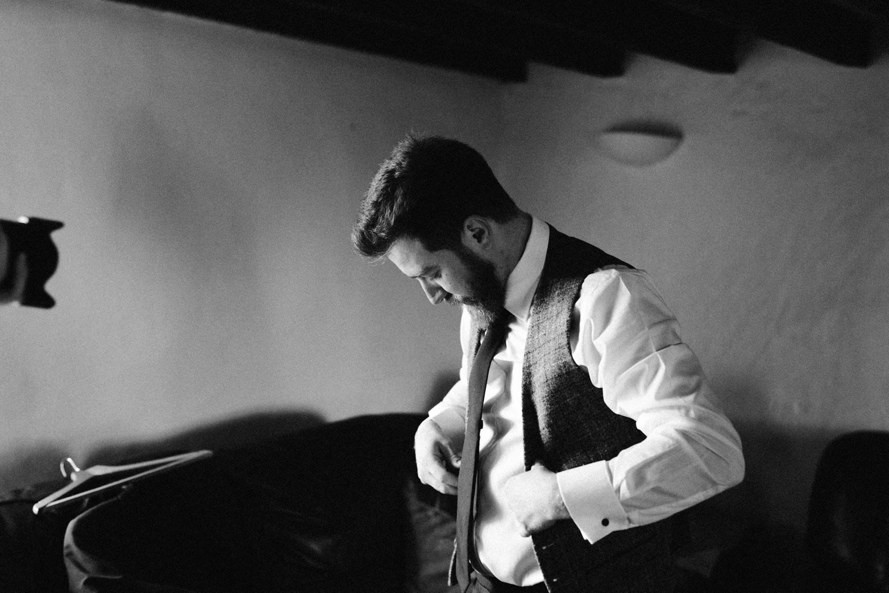 groom puts on his tweed waistcoat
