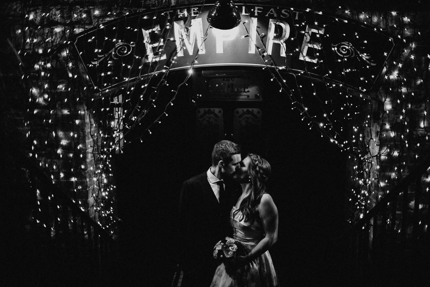 bride and groom pose for a romantic kiss under the sign of the empire music hall in belfast northern ireland