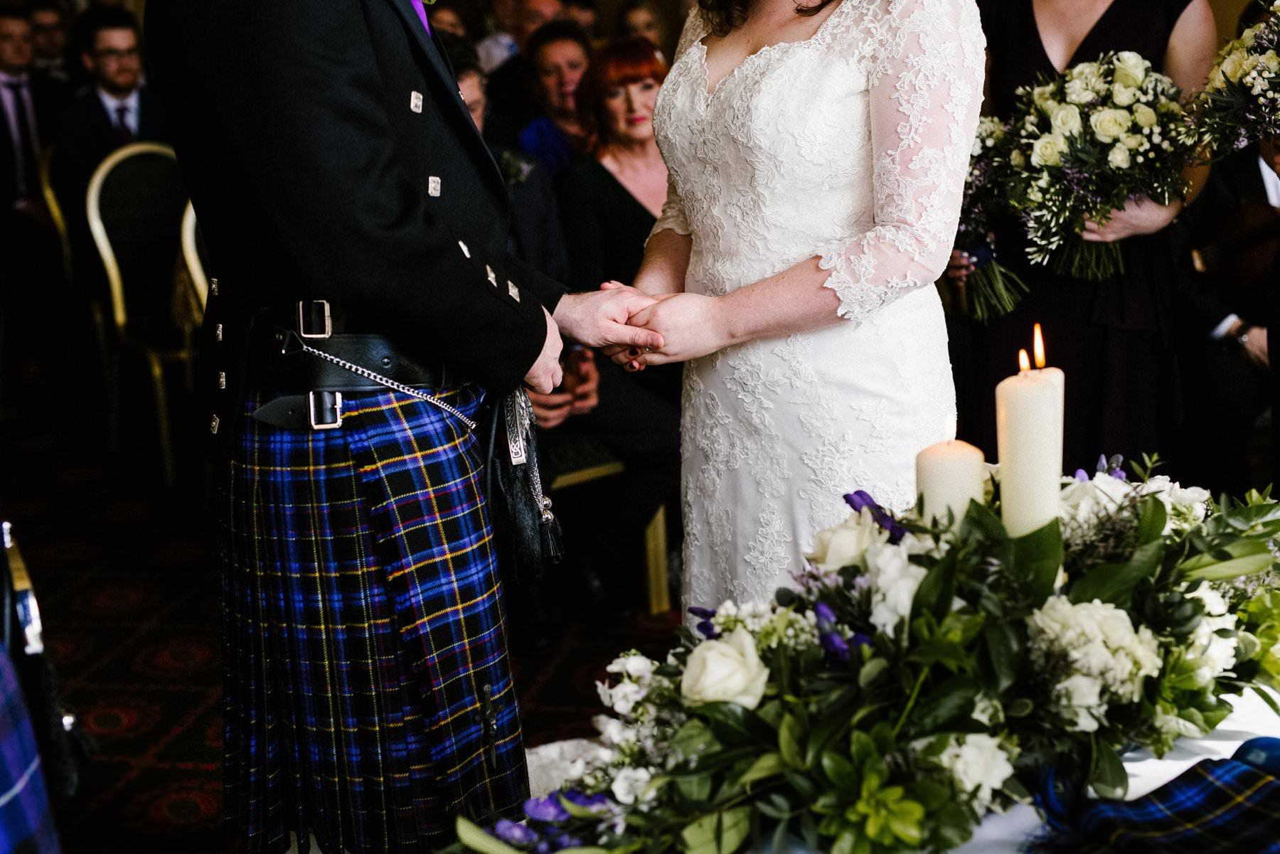 bride and kilt wearing groom exchange rings during wedding ceremony at Belfast Castle