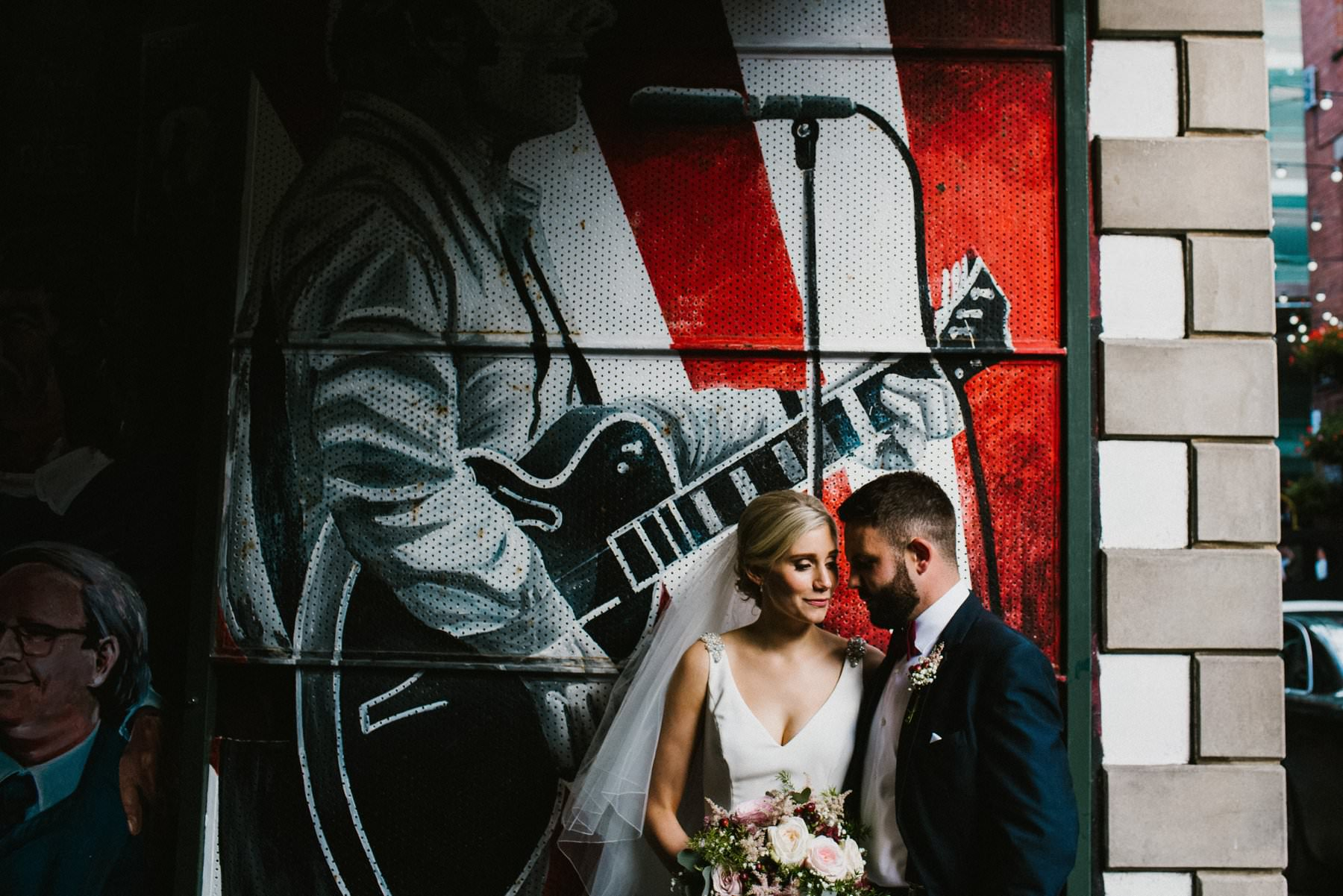 bride and groom pose for wedding portarit in Cathedral Quarter of Belfast