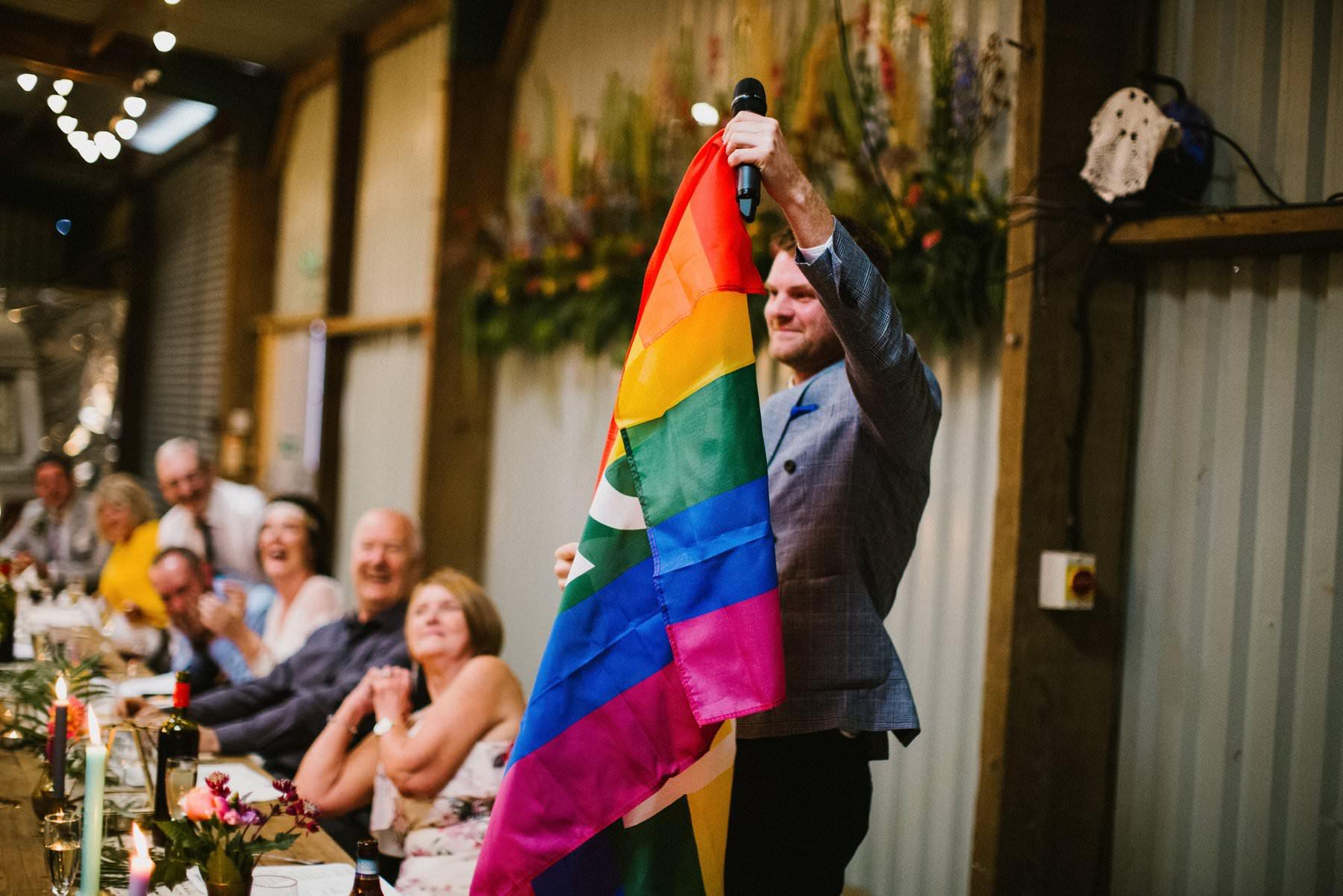 best man holding pride flag during speeches at wedding in Norfolk