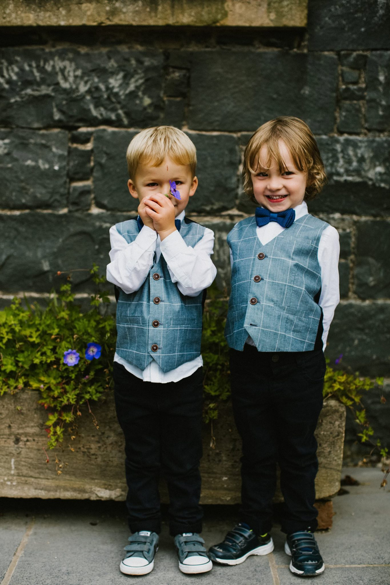 page boys in waistcoats show off a pansy they just plucked at Tullyveery House County Down