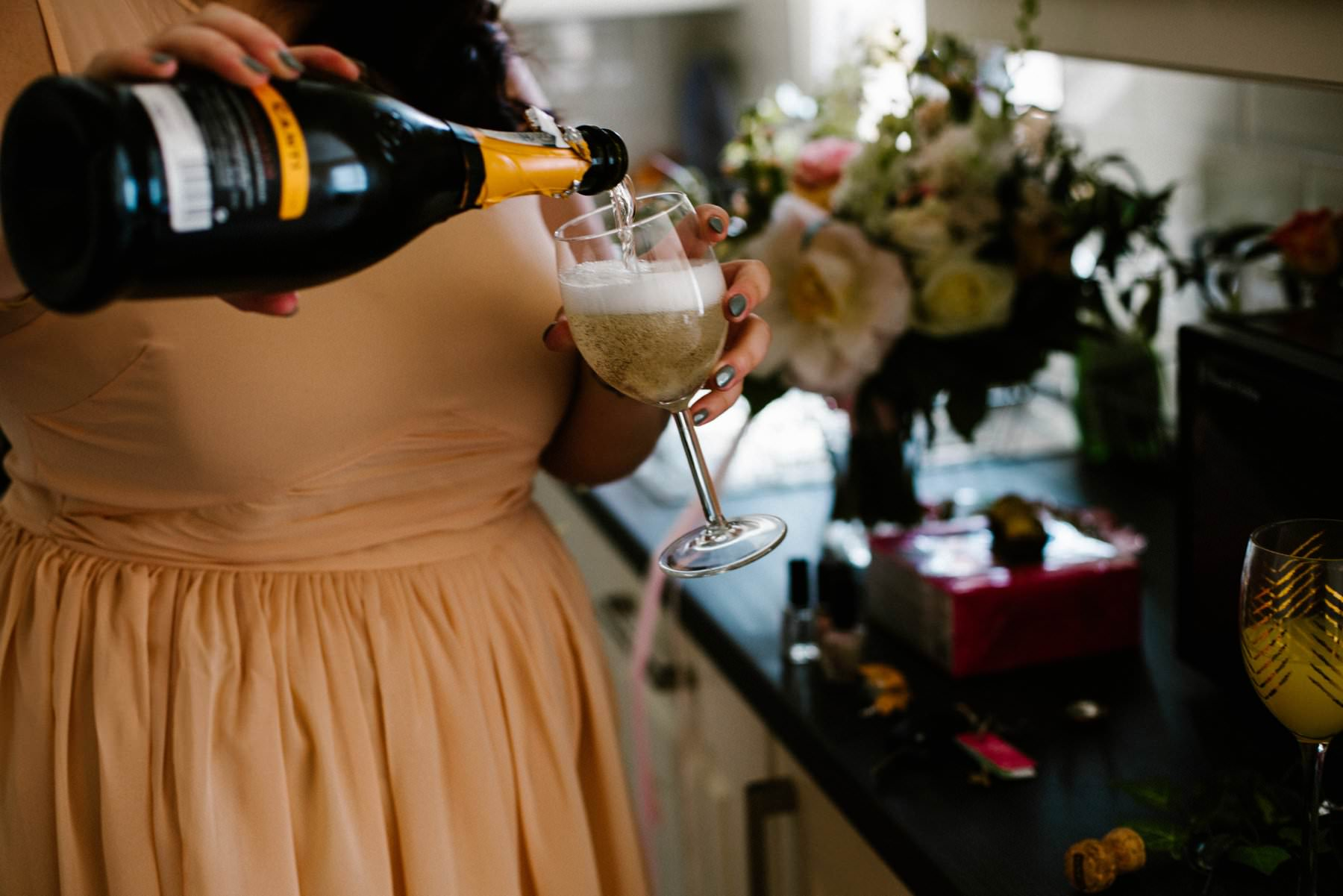 bridesmaid in peach dress pouring champagne