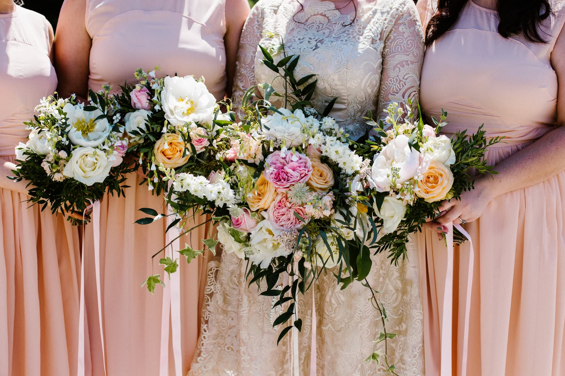 bride and bridesmaid show off wedding flowers