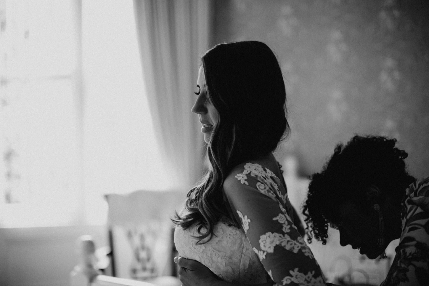 bride gets dressed for wedding at glenmore manor shot in black and white