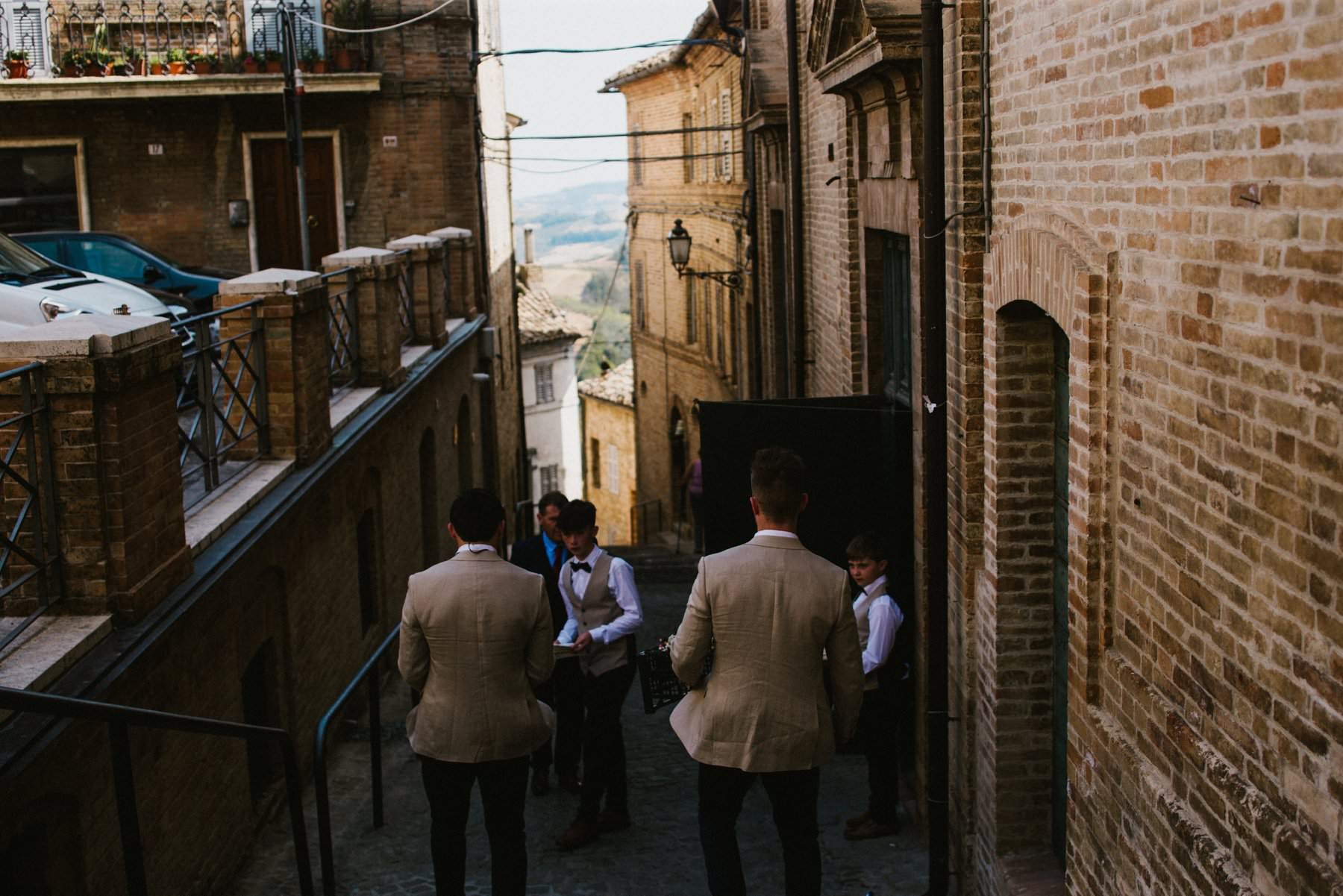 the groom arrive to the italian chapel in high in the italian countryside