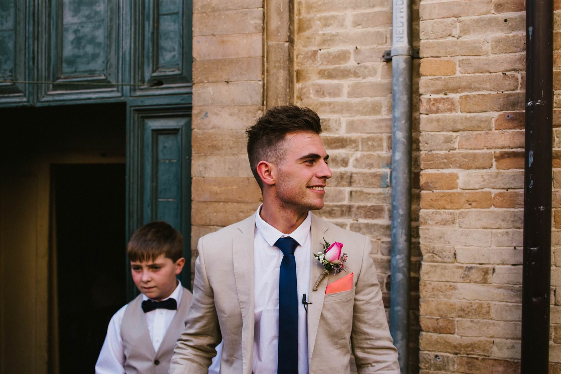 smiling groom in linen jacket and peach tie greets guests before his italian wedding