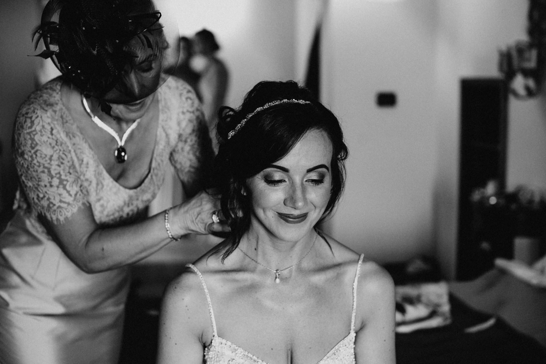 mother latches brides necklace before her petritoli wedding