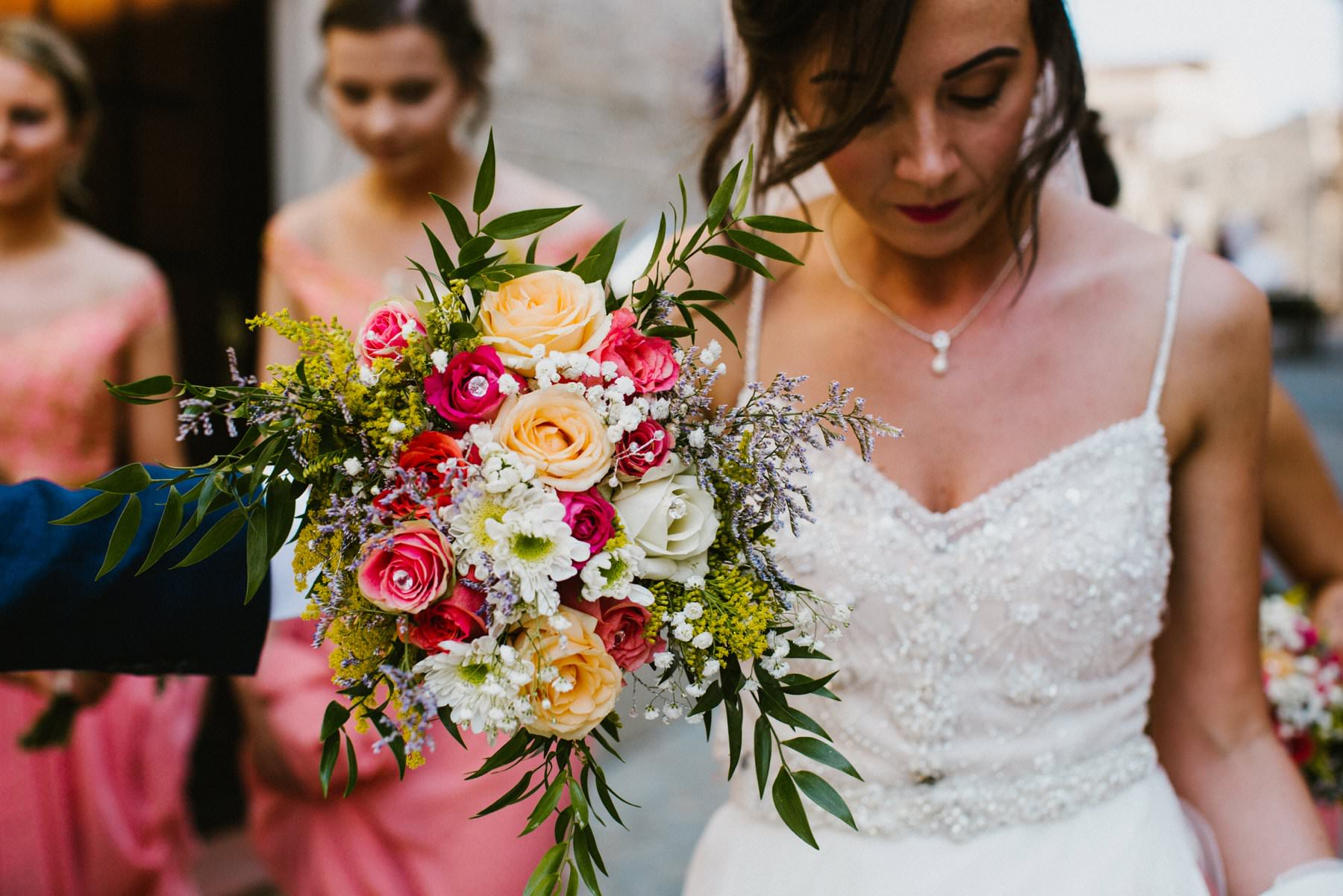 bride holds colourful pink, yellow and white bouquet before her italian wedding