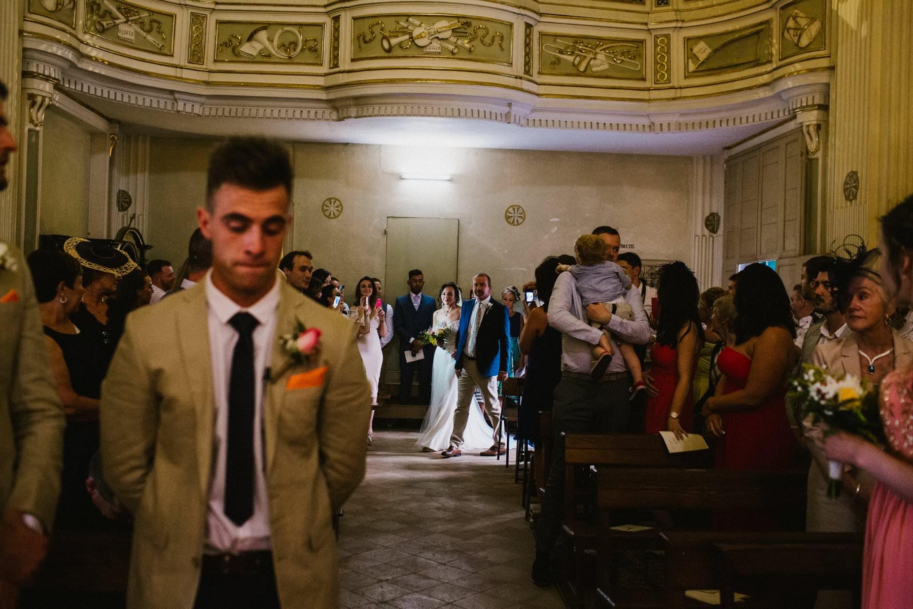bride enters the quaint italian chapel in petritoli