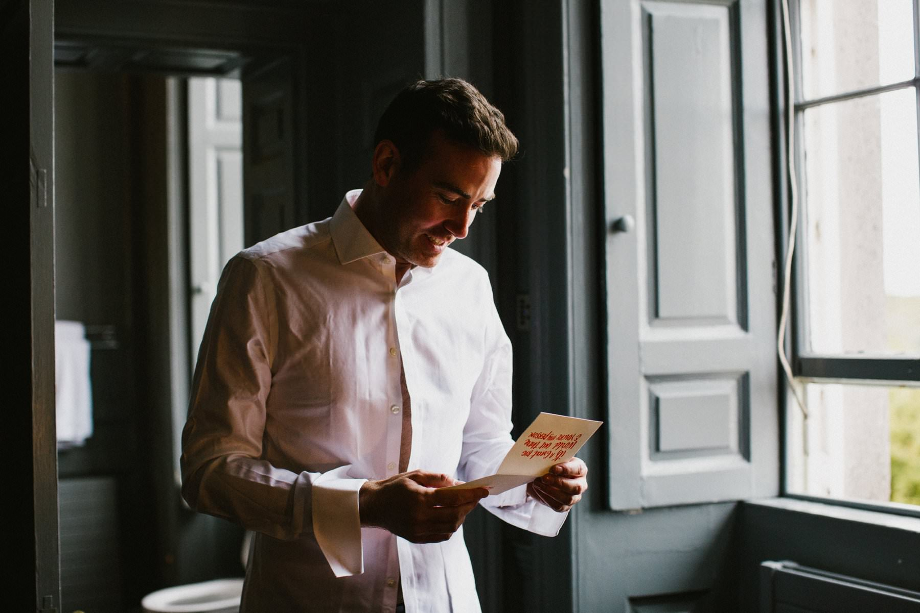 groom reads card from his husband to be by a window in Bellinter House Navan