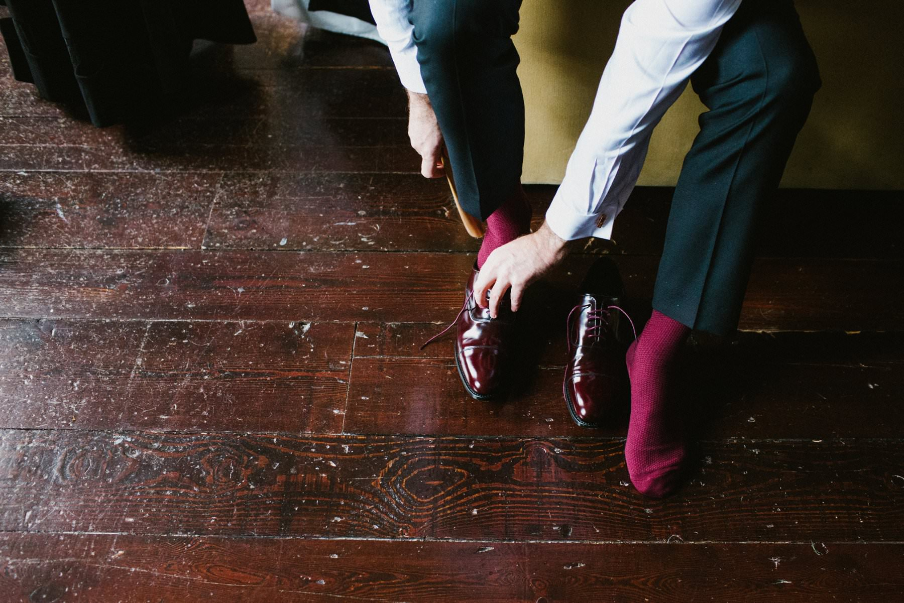 Groom puts on burgundy wedding shoes in Bellinter House Navan